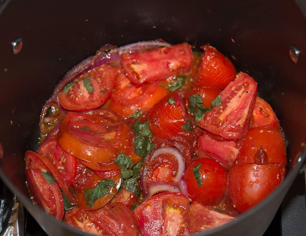 The tomato sauce simmering on the stove. Use a spoon to break the tomatoes apart in order to smooth out the sauce.