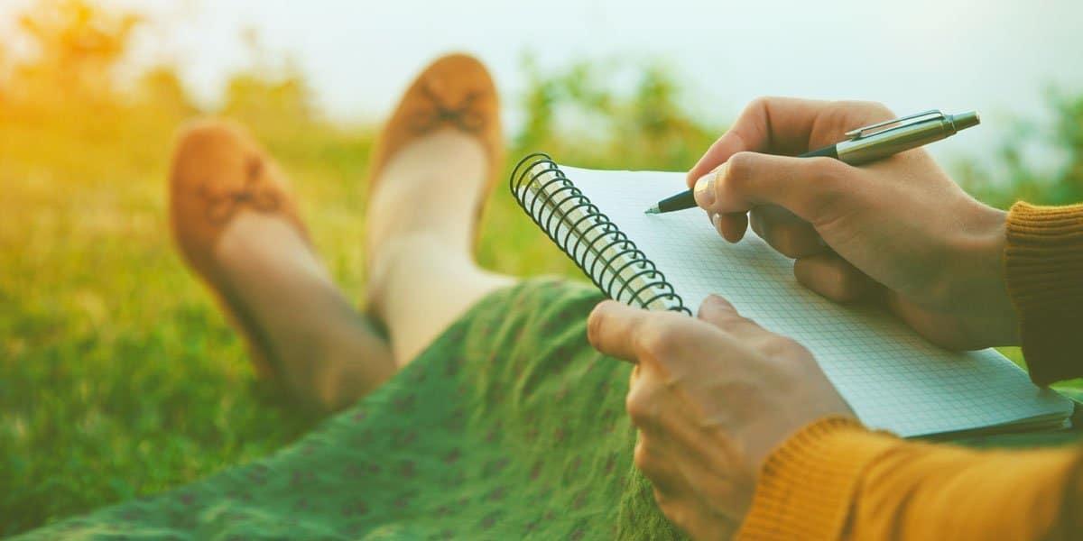 Woman journaling in a field