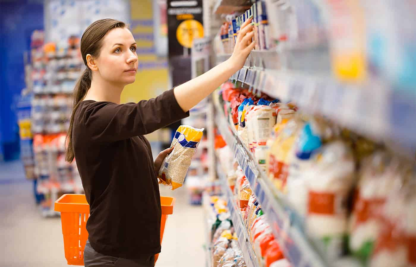 Woman shopping from the top shelf of the supermarket