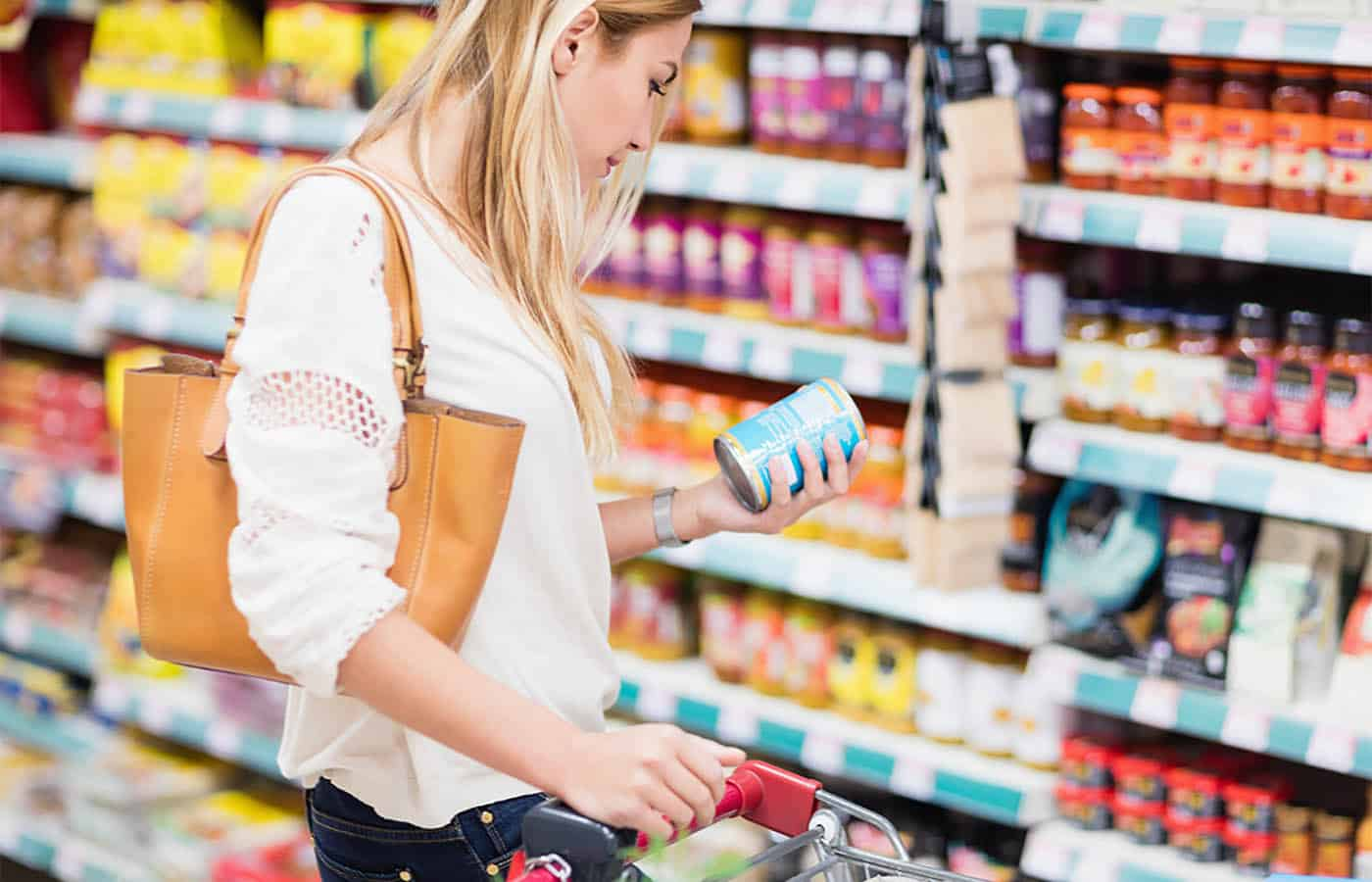 Woman carefully examining canned goods in grocery store