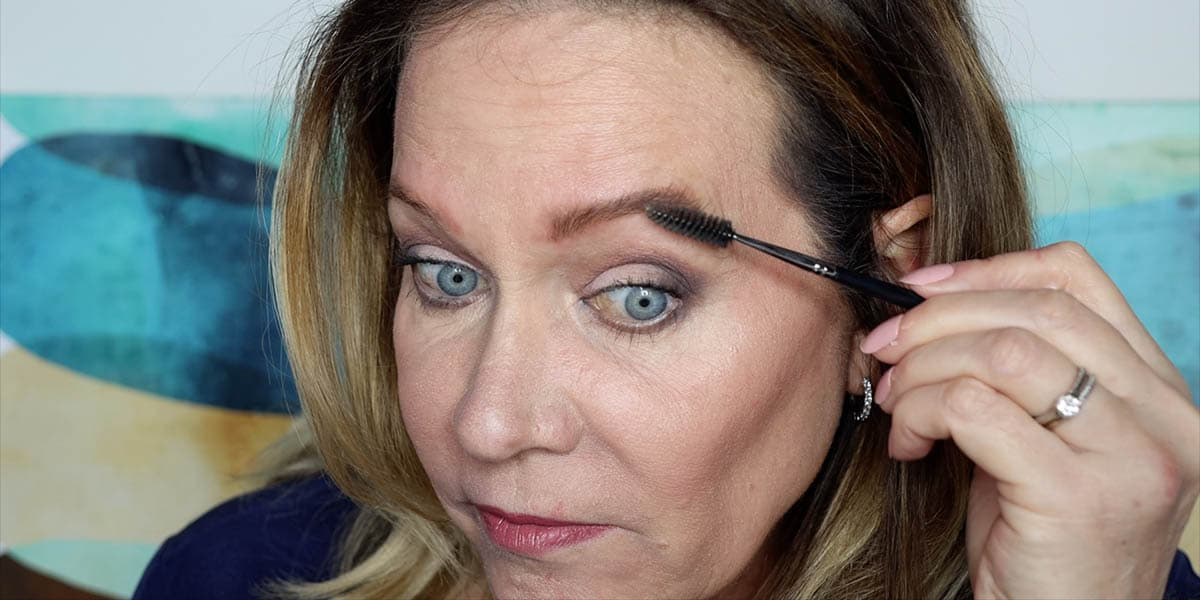 Brushing through filled in eyebrows to soften lines