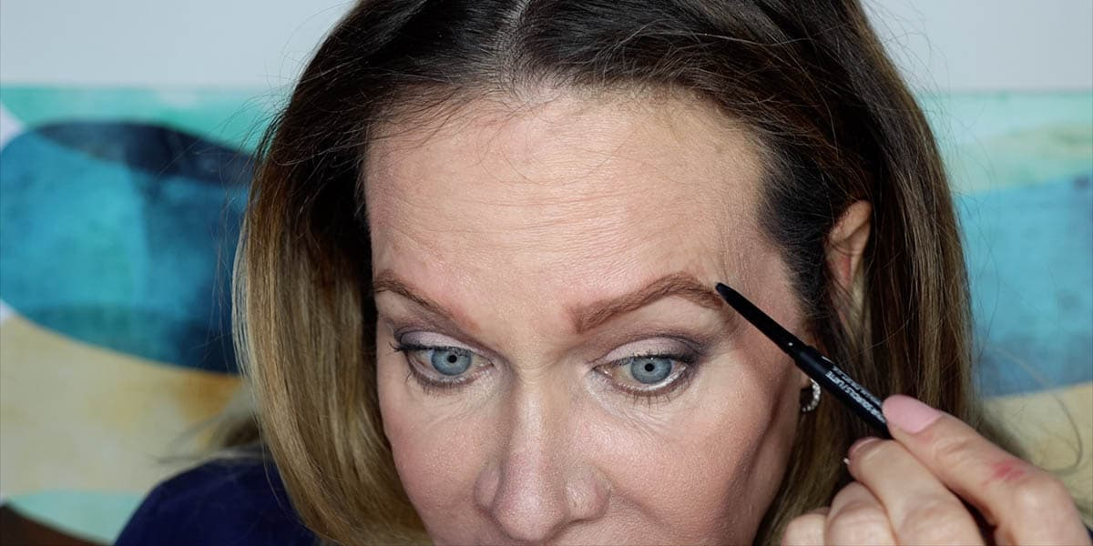 Using a brow pencil to connect the top brow line to the bottom line