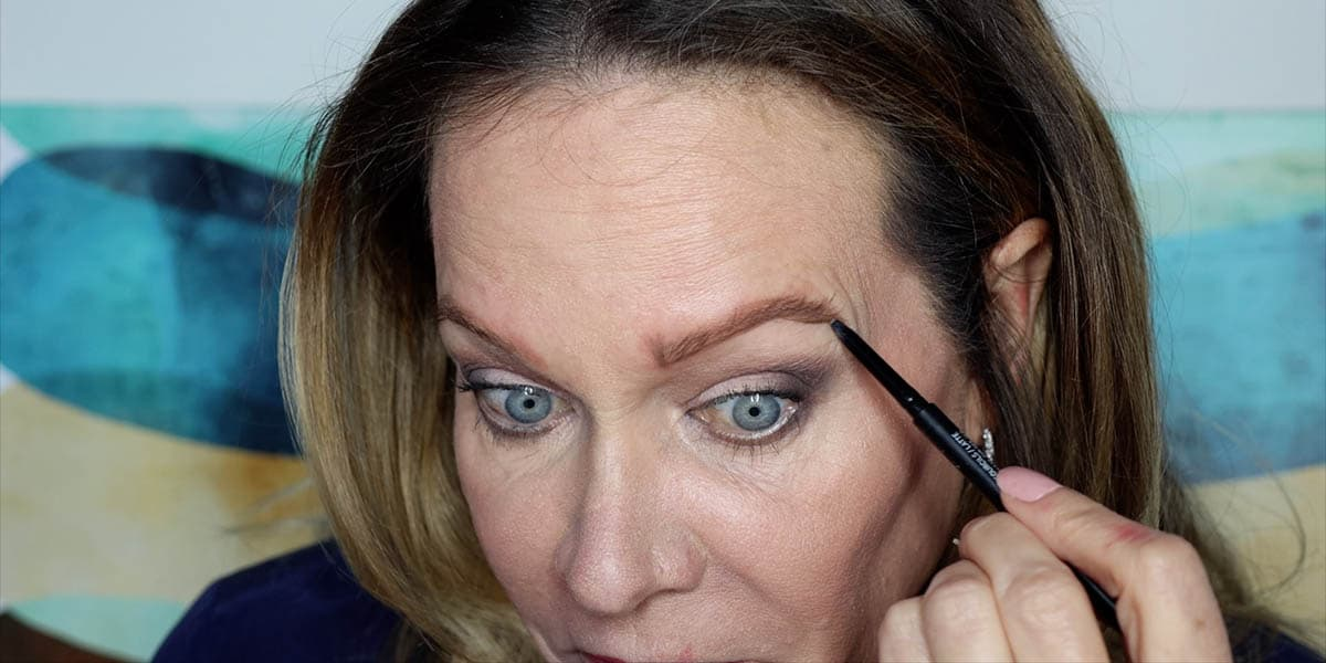 Connecting eyebrow placement dots with a thin line below the brow